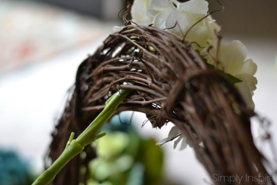 closeup of back of grapevine wreath with flower stem