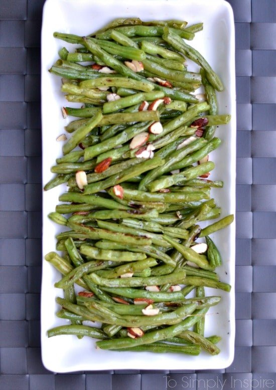 roasted green beans topped with sliced almonds a white plate