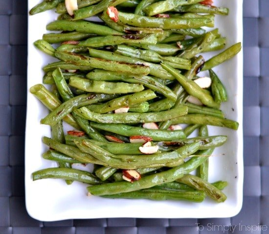Roasted green beans recipe topped with sliced almonds on a white rectangle plate