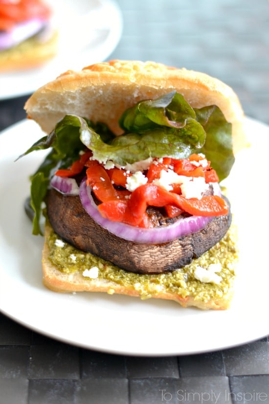 A close up of a open portobello Mushroom sandwich with lettuce, red peppers and red onion slice