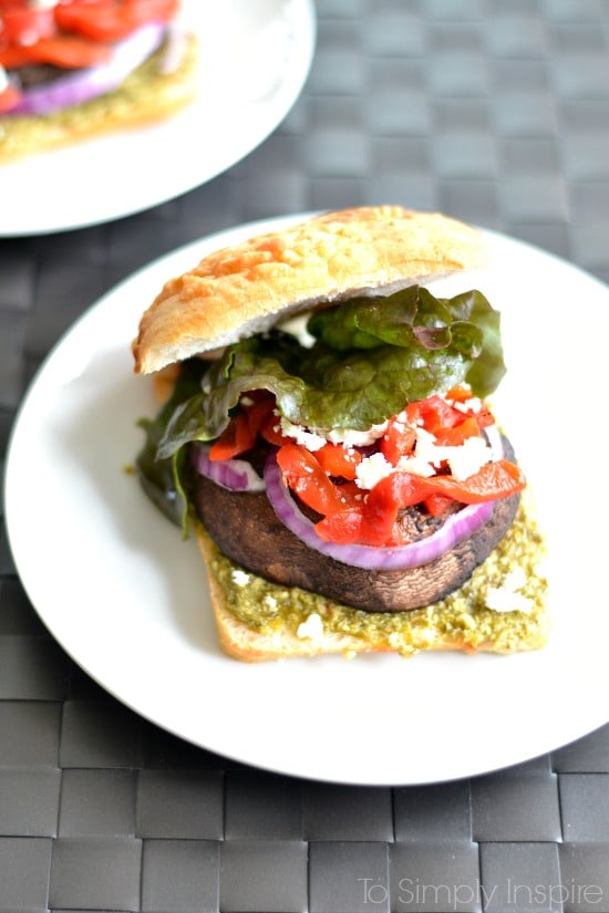A portobello Mushroom sandwich with lettuce, red peppers and red onion slice