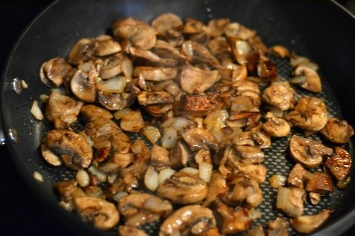 mushrooms and onions cooking in a black pan