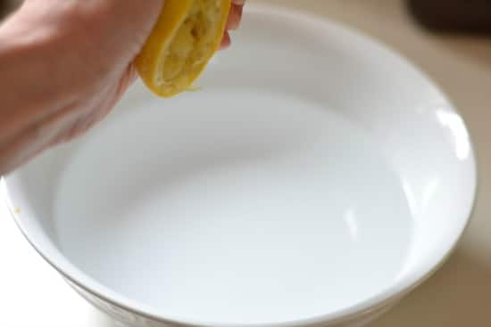 Squeezing lemon into a bowl of water