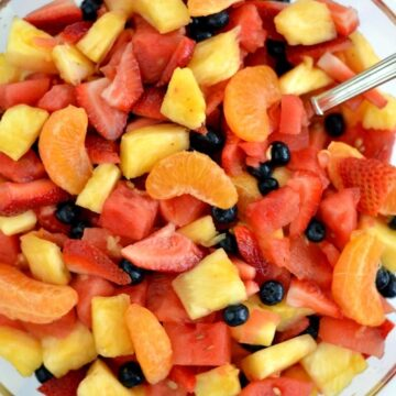 A bowl of oranges, watermelon, pineapple, strawberries and blueberries in a glass bowl with a spoon