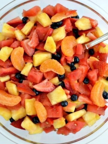 A bowl of oranges, watermelon, pineapple, strawberries and blueberries in a glass bowl -