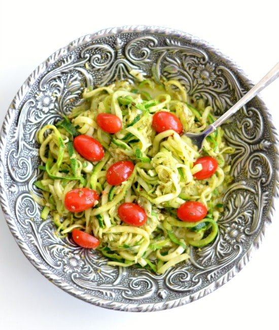 Pesto Zucchini Noodles with cherry tomatoes in a big silver serving bowl
