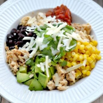 a white bowl with corn, avocado, black beans, salsa and cheese