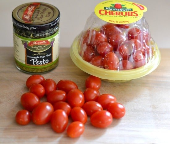 cherry tomatoes and a jar of pesto sauce on a cutting board
