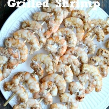 A plate of grilled shrimp on wooden skewers