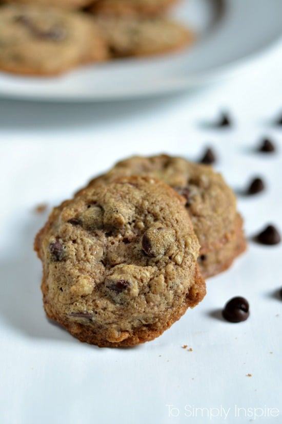 Oatmeal Chocolate Chip Cookies on a white table surrounded by chocolate chips