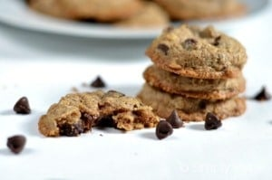 Three Oatmeal Chocolate Chip Cookies stacked on a white table with a plate