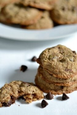 Three Oatmeal Chocolate Chip Cookies stacked on a white table with a plate of cookies in background