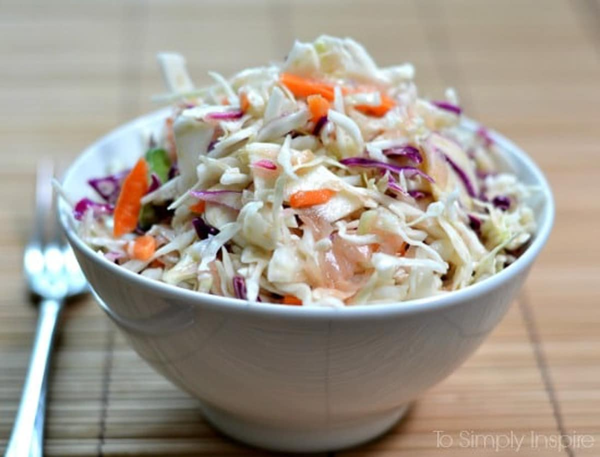 Ginger Sesame Slaw recipe in a white bowl on a bamboo placemat