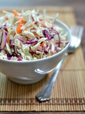 A closeup of a bowl slaw with a fork beside