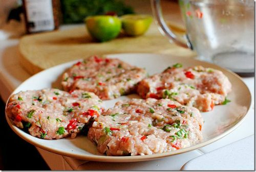 uncooked turkey burgers with red and green spices
