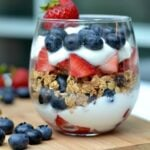 yogurt parfait layered with granola, strawberries and blueberries with text overlay