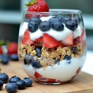 A glass layered with yogurt, blueberries, granola and strawberries on a wooden cutting board