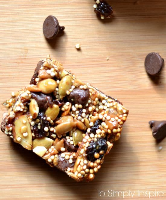 energy bar with quinoa almonds and pumpkin seeds on a wood cutting board with chocolate chips surrounding