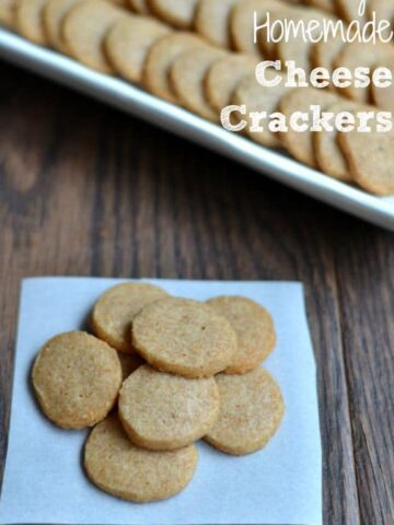 a bunch of round cheese crackers on a white napkin on a wood table.