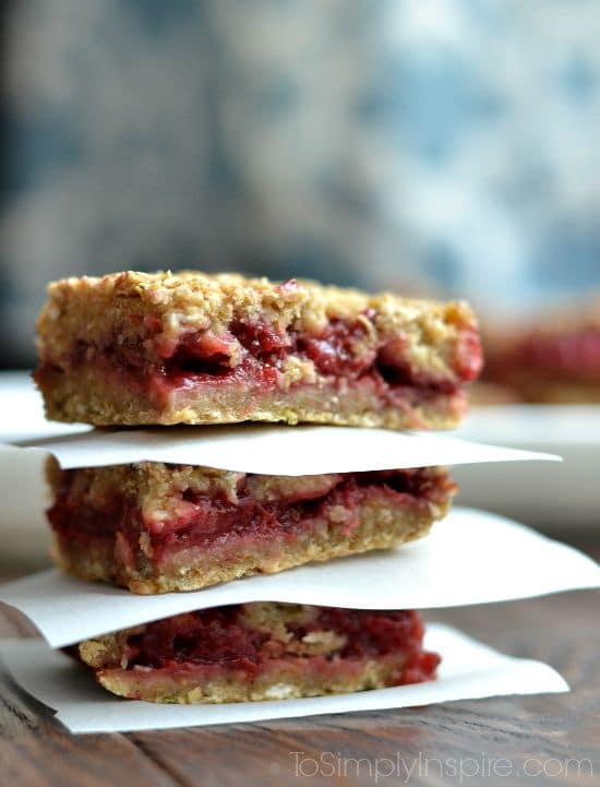 closeup of Three Strawberry Banana Oatmeal Bars stacked with parchment paper in between.