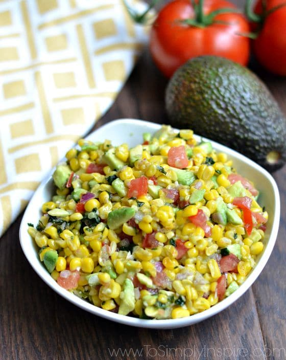 Corn Salsa recipe in a white bowl with an avocado and tomato beside it.