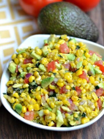 A white bowl of Corn Salsa with avocado beside