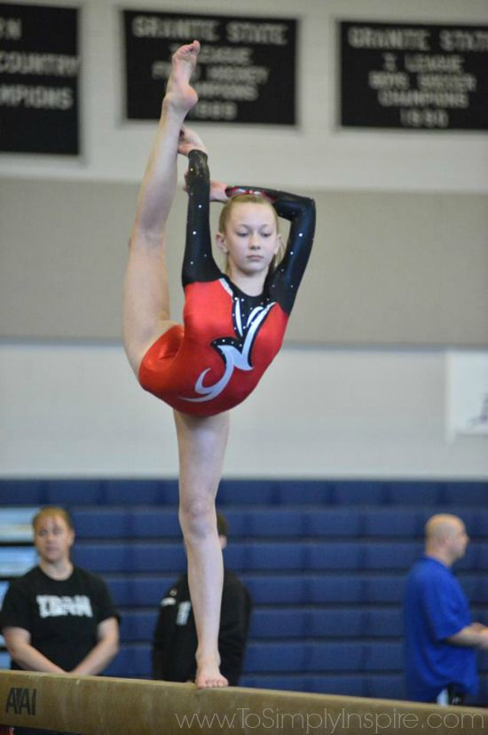A girl balancing on a one leg while holding the other leg