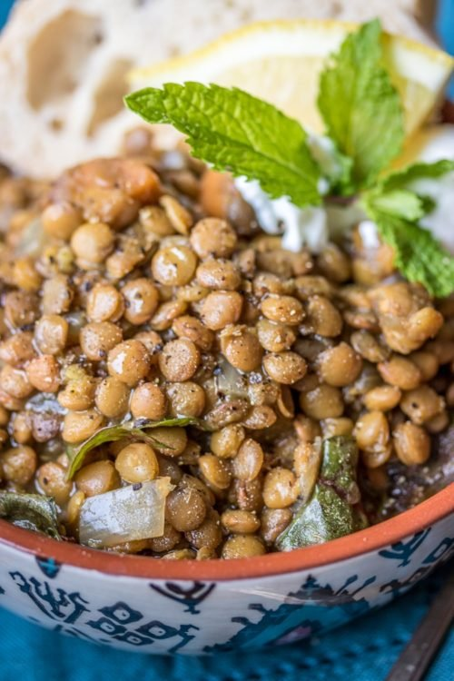 a bowl full of lentils with herbs