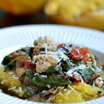 a white bowl with cooked spaghetti squash topped with cooked spinach, tomatoes, chicken and parmesan cheese