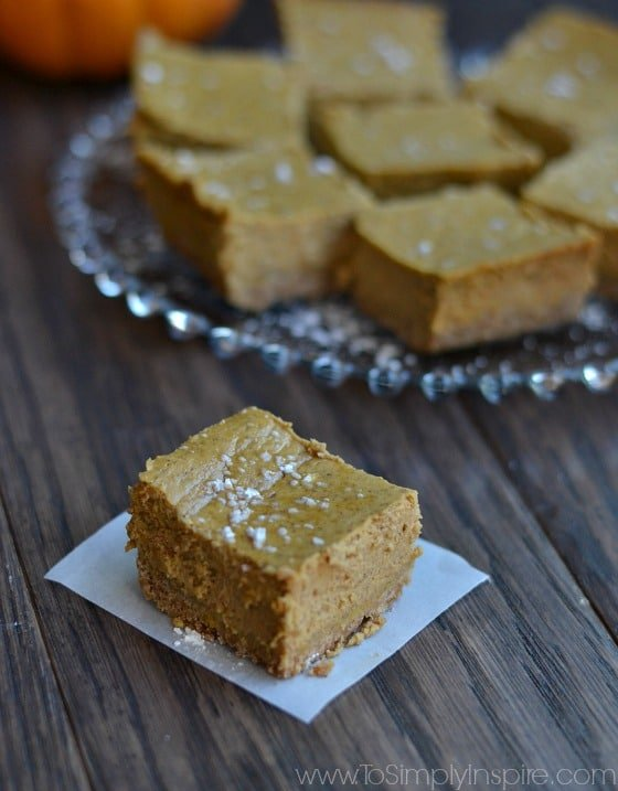 a square pumpkin cheesecake bar on a table with a plate full in the background
