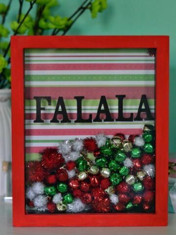 a red shawdow box frame filled with red green and white bells and pom moms that say FA LA LA in the front of the glass