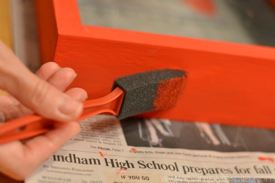 a piece of wood frame being painted red