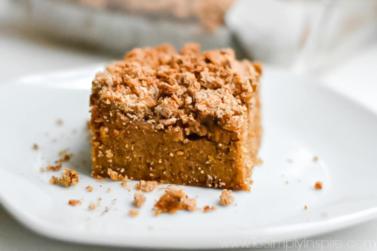 closeup of a slice of Pumpkin Coffee Cake on a white plate with baking dish in the background
