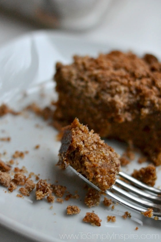 closeup of a bite of Pumpkin Coffee Cake on a fork on a white plate.