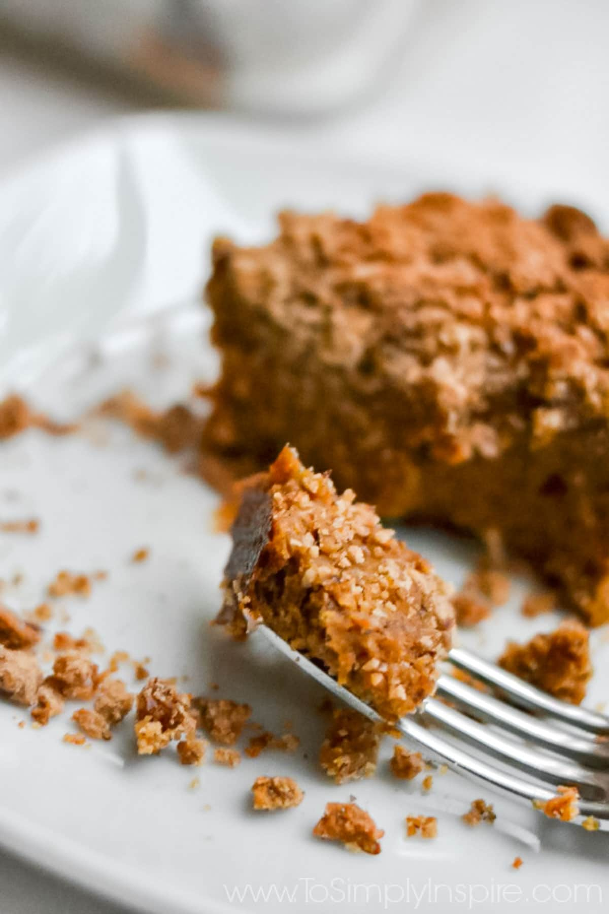 closeup of a bite of Pumpkin Coffee Cake on a fork laying on a white plate