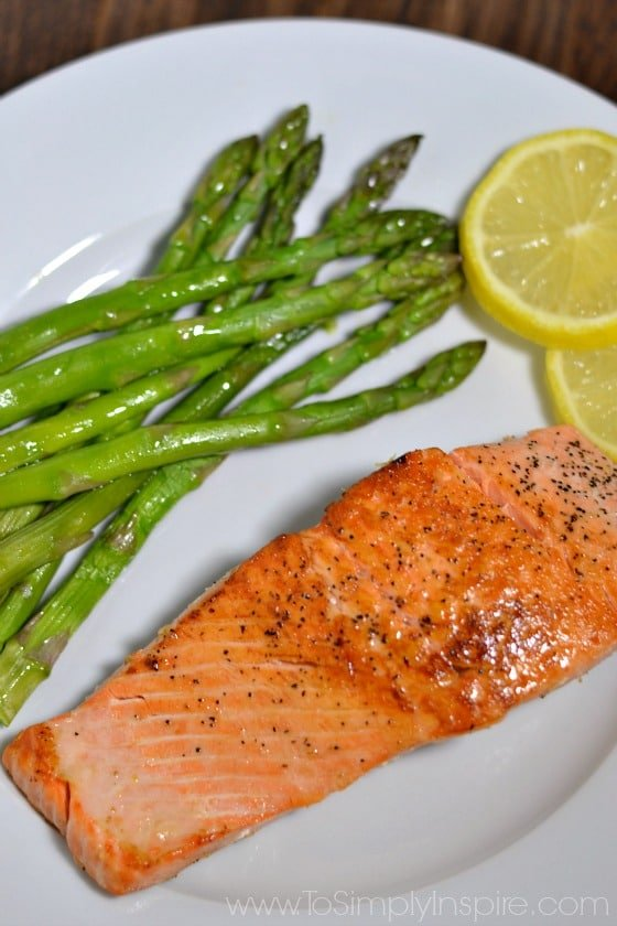 Pan Seared Salmon on a white plate with asparagus and lemon slices