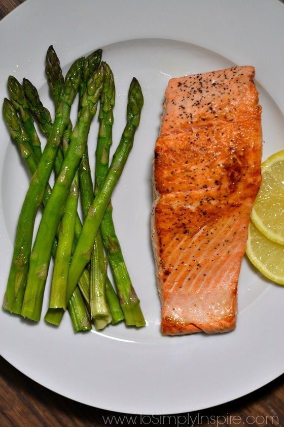 Pan Cooked Salmon on white plate with asparagus spears and lemon slices