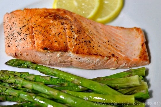 Pan Seared Salmon on a white plate with asparagus and 2 slices of lemon
