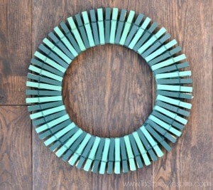 a wreath made out of painted green clothespins on a wood table