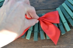 woman placing a red bow on a clothespin wreath