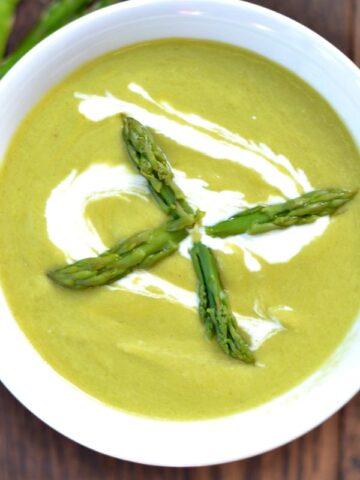 A closeup of a bowl of creamy asparagus soup