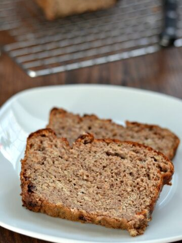 Two pieces of banana bread on white plate with a wire rack in background