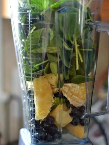 A blender filled with spinach oranges and blueberries