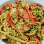 A plate of zucchini noodles, chicken and sliced red peppers