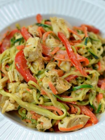 A white bowl of zucchini noodles, chicken and sliced red peppers