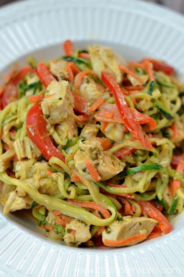 A closeup of zucchini noodles, chicken and sliced red peppers