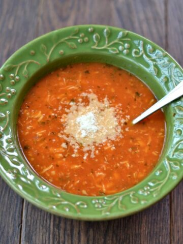A green bowl of chicken tomato soup with a spoon