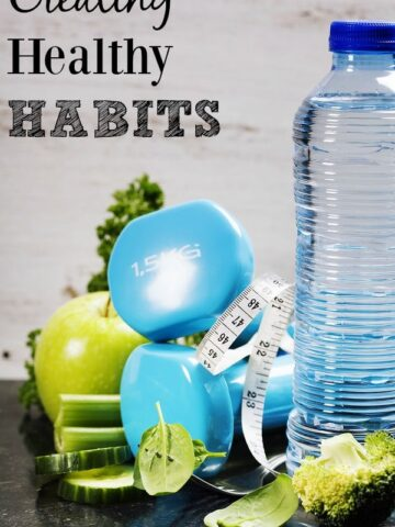 """A bottle of water with blue weights and a green apple with text overlay """"creating healthy habits"""""""
