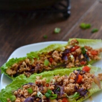 A plate of two lettuce wraps with ground turkey meat and red peppers