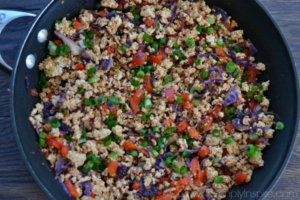 a black skillet with ground turkey, red peppers and scallions
